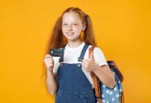 Dziewczynka trzyma kartę płatniczą dla dziecka
